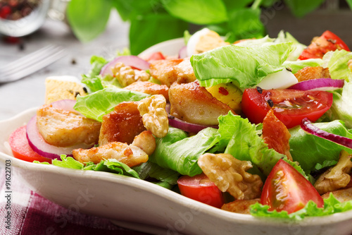 Photo Delicious salad with chicken, nuts, egg and vegetables.