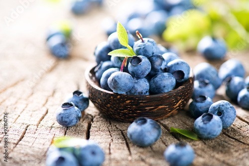 Canvas Juicy and fresh blueberries with green leaves in wooden bowl