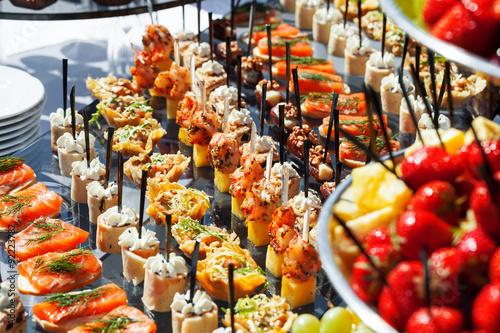 Fotomural Carne, pescado, canapés vegetales en una mesa al aire libre de la boda de fiesta