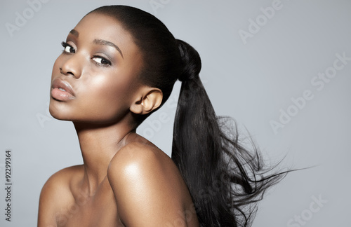 Portrait of beautiful serene African girl over grey studio background. African beauty with makeup and long hair.