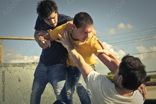 Three young guys in a fight Fototapete