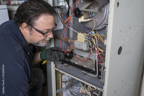 Canvas Print Technician Looking Over A Gas Furnace