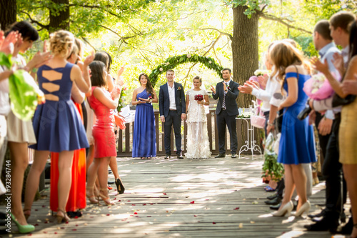 Fotografiet outdoor wedding ceremony at park with lot of guests