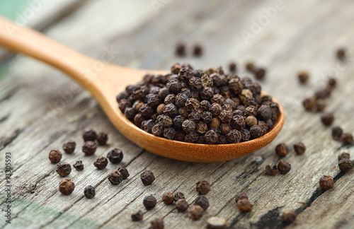Stampa su Tela Whole black pepper on wooden spoon