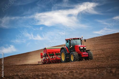 Obraz na plátně Farmář s traktorem setí plodin na poli