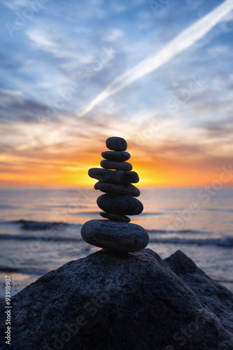 Stable vertical cairn at sunset on the sea