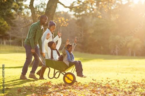 Carta da parati Young parents holding their children in a wheelbarrow