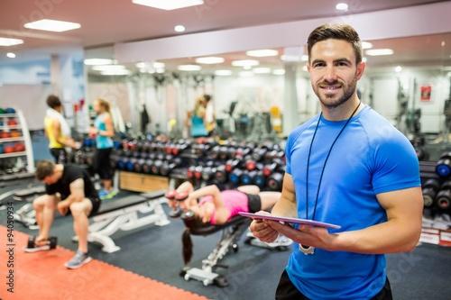 Fotografie, Tablou Handsome trainer using tablet in weights room