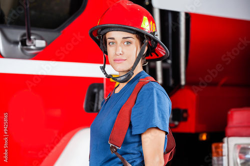 Canvas-taulu Portrait Of Confident Firewoman Wearing Red Helmet