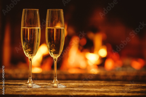 Wallpaper Mural Two glasses of sparkling champagne in front of warm fireplace