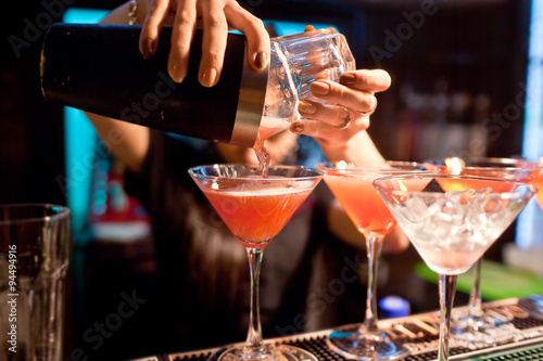 The girl bartender prepares a  cocktail in the nightclub