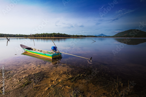 Fototapeta The beautiful reflection of sampan and hill at the lake