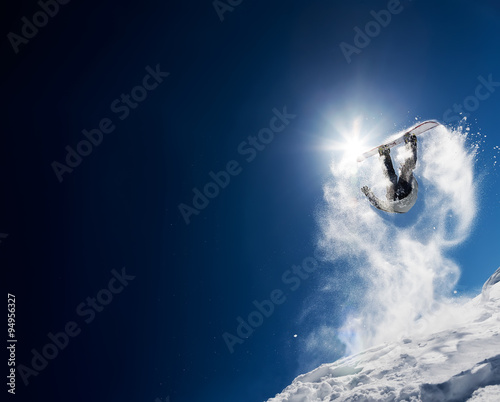 Snowboarder making high jump in clear blue sky. Concept: fun, sport, courage, adventure, danger, extreme. Large copy space on the left side.
