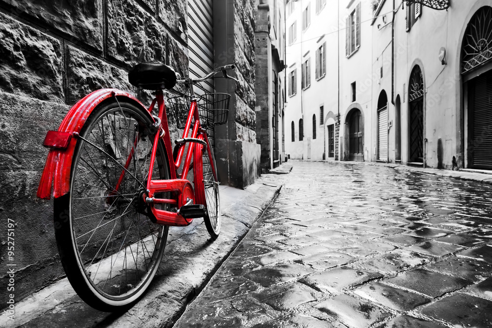 Retro vintage red bike on cobblestone street in the old town. Color in black and white