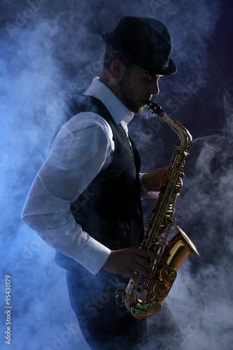 Fototapeta Elegant saxophonist plays jazz on dark background in blue smoke