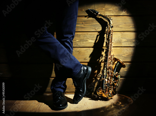 Fotografia The musician with sax on wooden background, close up