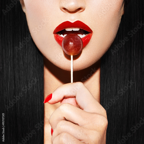 Stampa su Tela Sexy woman with red lips holding lollipop