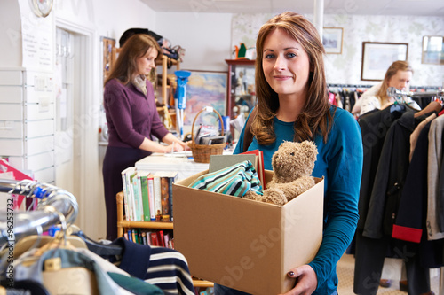 Woman Donating Unwanted Items To Charity Shop Fototapet
