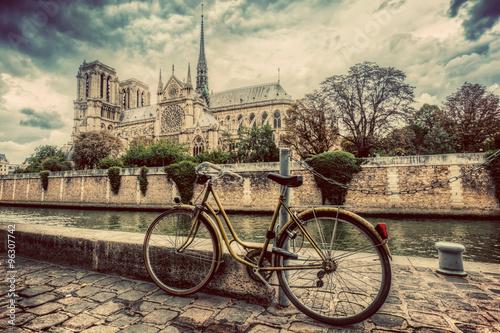Fotografia Retro bike next to Notre Dame Cathedral in Paris, France. Vintage