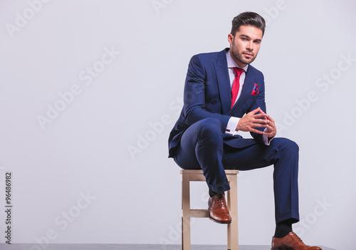 Carta da parati elegant man sitting in studio palms touching while resting his l