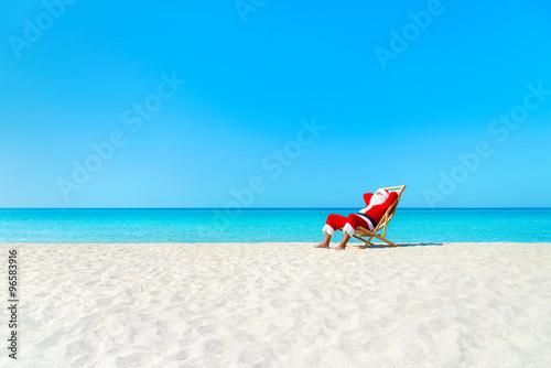 Fotografia Christmas Santa Claus resting on sunlounger at ocean sandy tropical beach