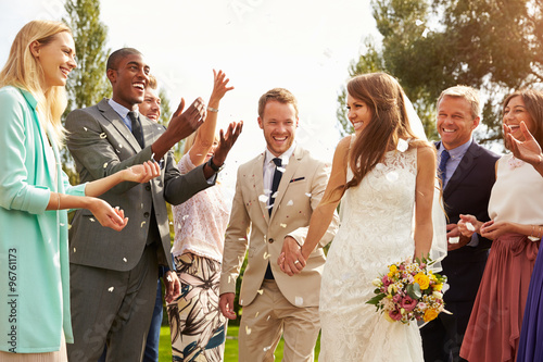 Valokuva Guests Throwing Confetti Over Bride And Groom At Wedding
