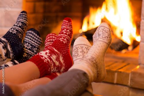Photo Feet in wool socks near fireplace in winter time
