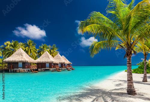 Leinwand Poster Über Wasser Bungalows auf einer tropischen Insel mit Palmen und am