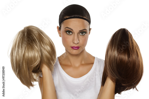 Fotografia young woman with a wig cap make a comparison between two wigs
