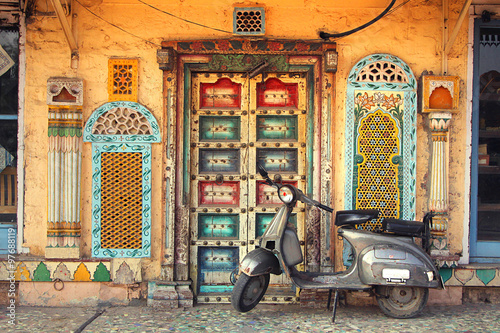 Motorcycle parked next to an ornate wall Fototapeta