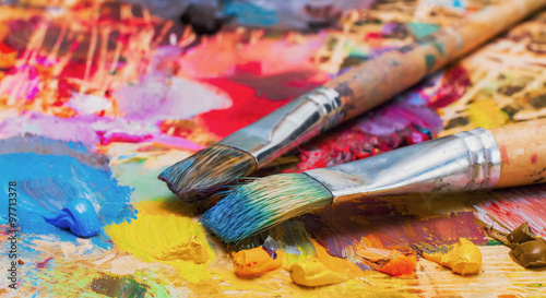 Photo Used brushes on an artist's palette of colorful oil paint