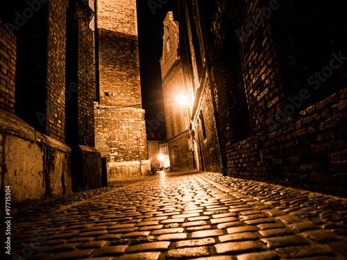 Fotografia, Obraz Illuminated cobbled street in old city by night