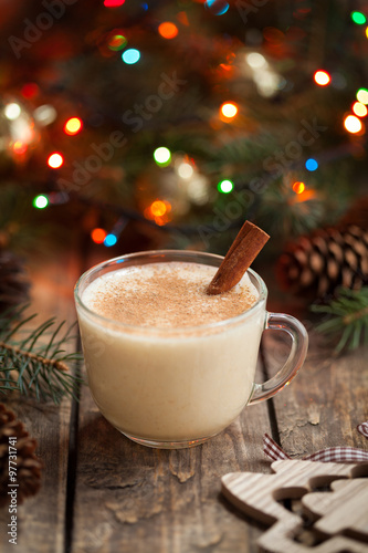 Eggnog traditional christmas holiday egg, vanilla, rum alcohol liqueur drink preparation recipe in two glass cups with cinnamon sticks on wooden vintage table. Colorful bokeh background. shallow depth #97731741
