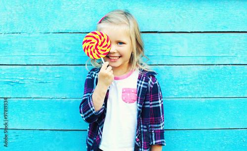 Obraz na płótnie Happy smiling child with sweet lollipop having fun over colorful