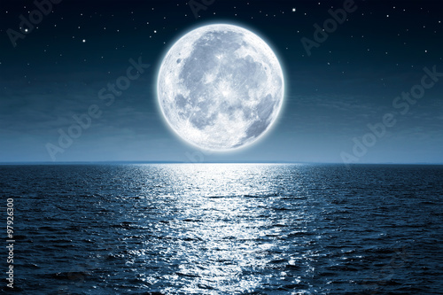 Canvas Print Full moon rising over empty ocean at night with copy space