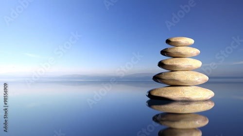 Photo Zen stones stack from large to small  in water with blue sky and peaceful landscape background