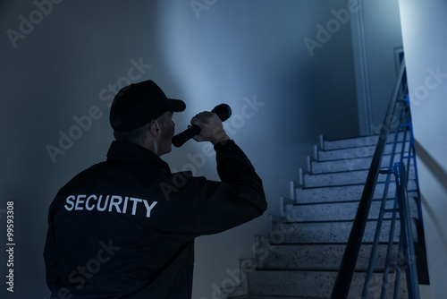 Slika na platnu Security Guard Searching On Stairway With Flashlight