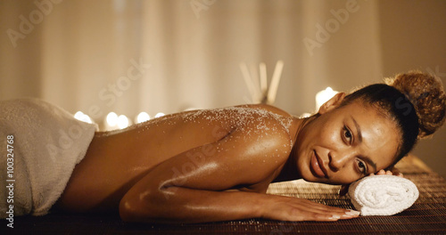 Fotografie, Obraz Smiling young woman lying on massage table with salt scrub on back in the health