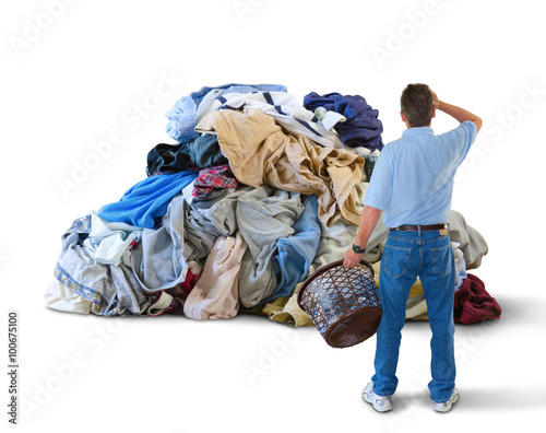 Fototapeta A distraught man with his hand to his head and a laundry basket in his hand is s