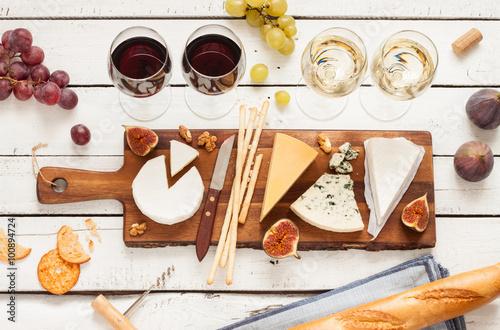 Fotografia Czerwone i białe wino oraz różne rodzaje serów (cheeseboard) na prosty drewniany stół