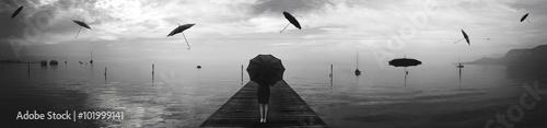 elegant woman repairing from the rain of blacks umbrellas