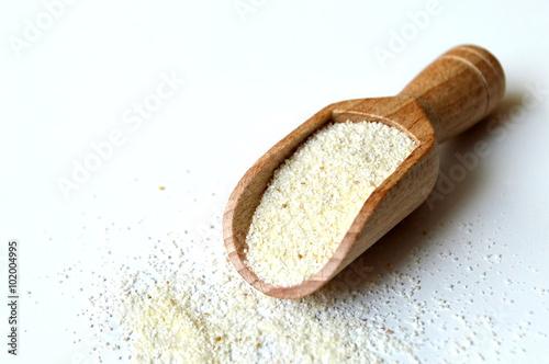 Semolina flour in wooden scoop