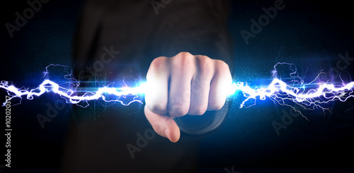 Tablou Canvas Business man holding electricity light bolt in his hands