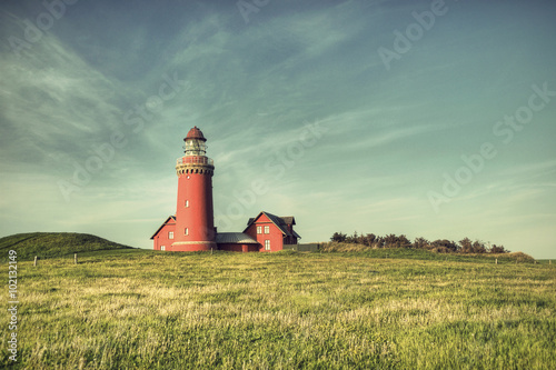 Photo beautiful red Lighthouse Bovbjerg Fyr with green grass and blue sky in vintage f