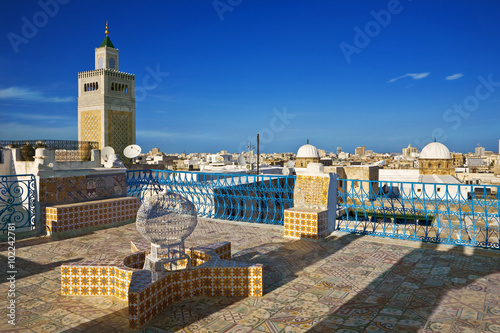 Tunisia. Tunis - old town (medina). Terrace of Palais d'Orient with ornamental wall covered tiles. There is minaret Zitouna Mosque on left side