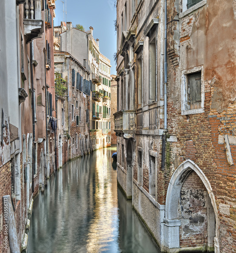 typical narrow canal with old colorful brick houses in Venice, Italy, Europe