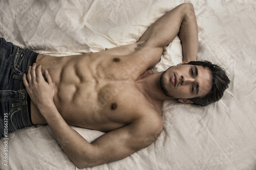 Canvas Print Shirtless sexy male model lying alone on his bed