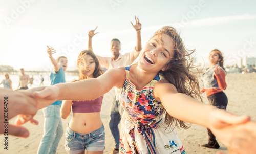 Obraz na płótnie Group of friends having fun and dancing on the beach