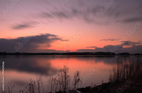 Obraz na plátně Zonsondergang in het Twiske reacreatiegebied met spiegelend meer