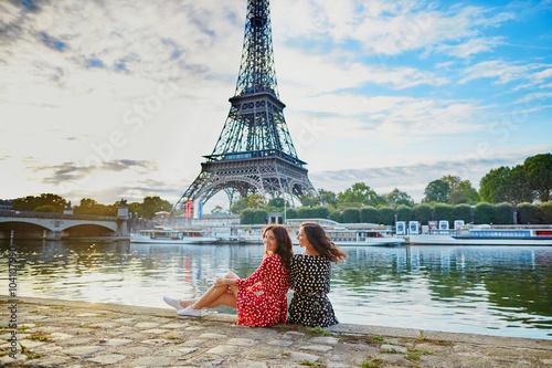 Fototapeta Beautiful twin sisters near the Eiffel tower in Paris, France